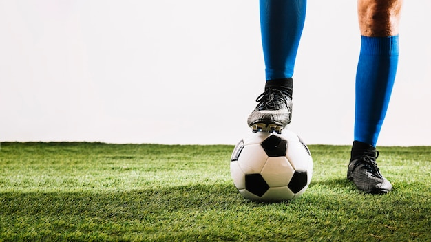 Crop nogi i piłka na polu