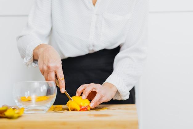 Crop person slice fruit