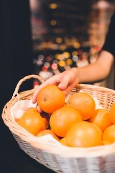 Crop ręka bierze pomarańcze od kosza