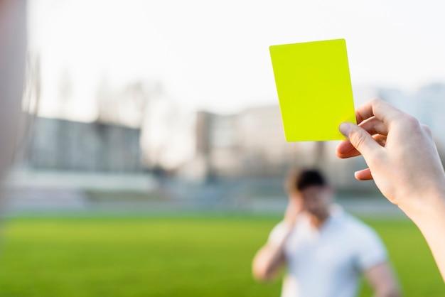 Crop ręka pokazuje żółtą kartkę