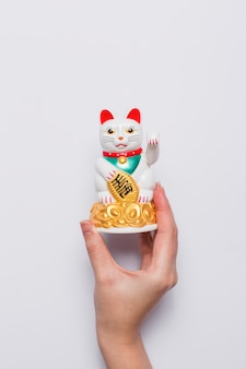 Crop ręka trzyma chińskiego szczęsliwego kota