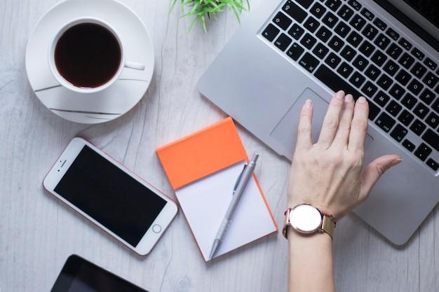 Crop ręka używać laptop blisko kawy i smartphone