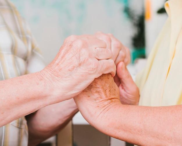 Crop starsza para trzymając się za ręce