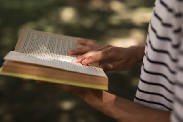 Crop studencka czytelnicza książka w parku