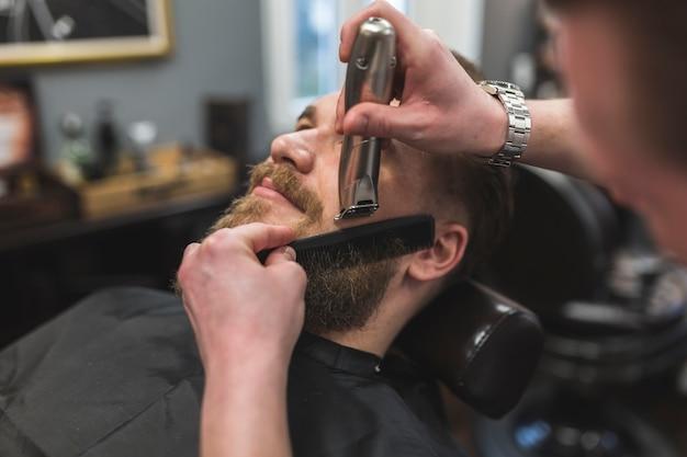 Crop stylista przycina brodę mężczyzny