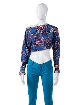 Crop top z turkusowymi spodniami. żeński manekin w crop top. stylowy asymetryczny top dla kobiet. nowa wizytówka w sklepie.
