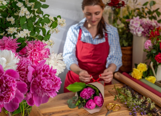 Crop view szklany wazon z kwitnącymi piwoniami sprzedawca kwiatów biznes florystyczny