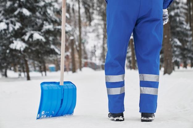 Cropped cleaner z łopatą na śniegu w parku.