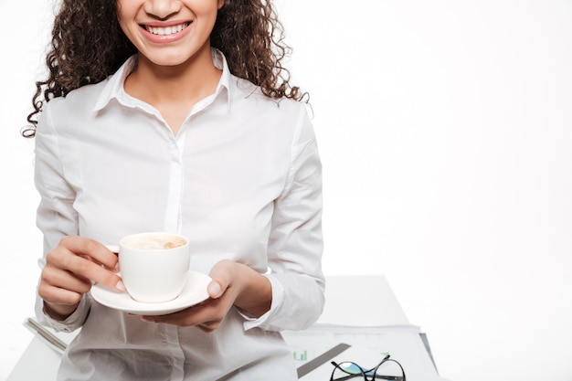 Cropped fotografia szczęśliwa afrykańska biznesowa kobieta pije kawę