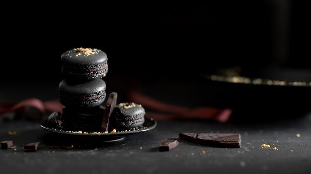 Cropped strzał ciemnej czekolady macarons na czarnym talerzu na zmroku stole