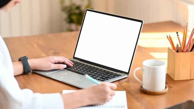 Cropped strzał młody projektant kobiety writing na notatniku podczas gdy ona siedzi białego pustego ekranu laptop i używa przy nowożytnym drewnianym stołem. koncepcja życia kobiet.