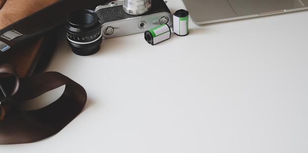 Cropped strzał nowożytny fotograf z copyspace i biurowymi dostawami na białym drewnianym stole