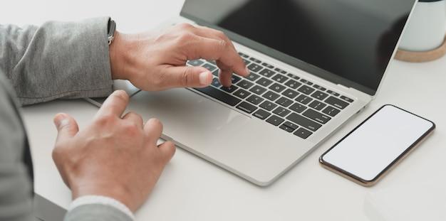 Cropped strzał pomyślny biznesmen pracuje nad jego projektem podczas gdy pisać na maszynie na laptopie