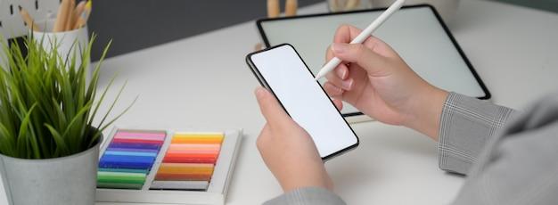 Cropped strzał pracuje na egzaminu próbnego smartphone i pastylce na bielu stole profesjonalny projektant