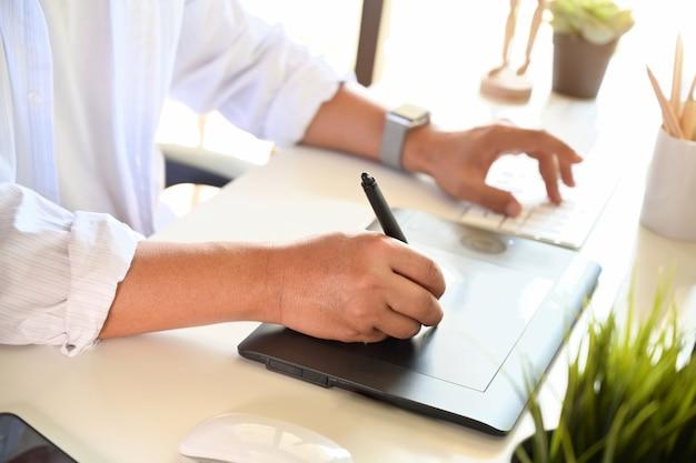 Cropped strzał projektant pracuje z cyfrową rysunkiem kreśli pastylkę dla kreatywnie projekta w biurze