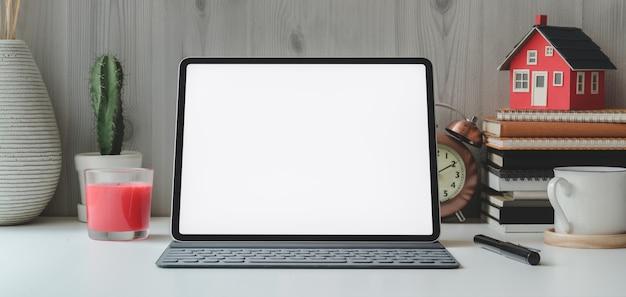 Cropped strzał pustego ekranu cyfrowa pastylka i biurowe dostawy na bielu stole i drewnianej ścianie