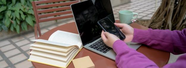 Cropped strzał żeński student uniwersytetu używa smartphone podczas gdy pracujący z laptopem i książkami