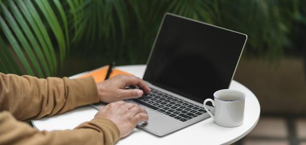 Cropped strzału młody człowiek pracuje nad jego projektem z laptopem i biurowymi dostawami na bielu stole