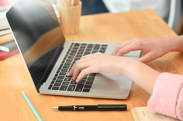Cropped strzału żeńskiego ucznia ręki używać laptop na drewno stole.