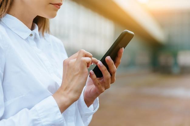 Cropped widok bizneswoman używa telefon. pomyślny żeński przedsiębiorca sprawdza emaila na telefonie. żeńska wiadomość sms. . t.