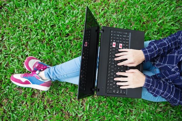 Cropped widok dziewczyna pracuje na laptopa na trawie