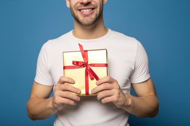 Cropped widok uśmiechnięty mężczyzna mienia prezent odizolowywający na błękicie
