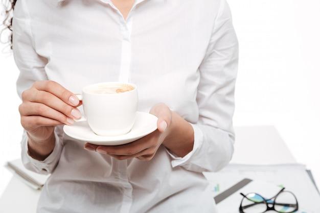 Cropped wizerunek afrykańska biznesowa kobieta pije kawę
