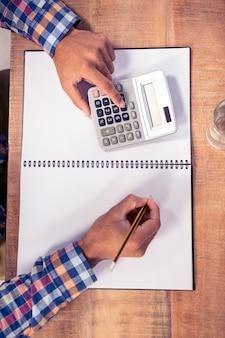 Cropped wizerunek biznesmen używa kalkulatora podczas gdy pisać na książce przy biurkiem