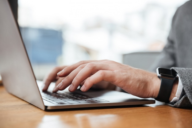 Cropped wizerunek biznesmena obsiadanie stołem w kawiarni i używać laptop