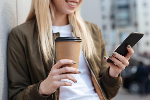 Cropped wizerunek blondynki kobieta używa smartphone