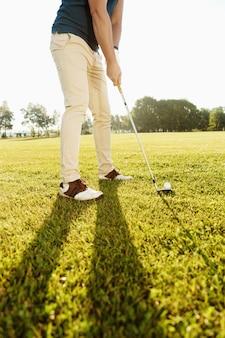 Cropped wizerunek golfisty kładzenia piłka golfowa na zieleni