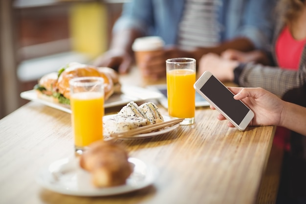 Cropped wizerunek kobieta używa telefon podczas gdy mieć śniadanie w biurze