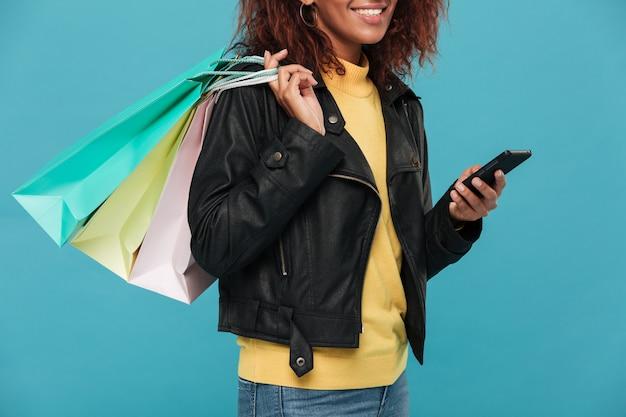 Cropped wizerunek kobiety mienia torba na zakupy i telefon.