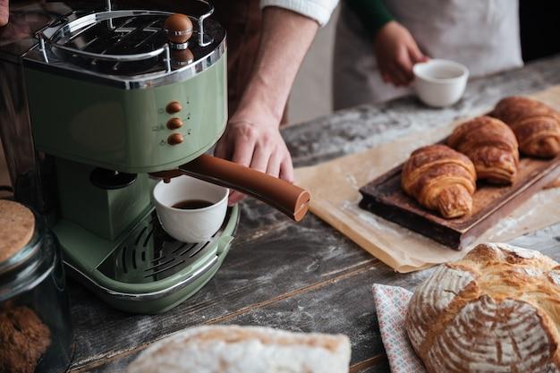 Cropped wizerunek młodzi piekarzi stoi przy piekarnią pije kawę.