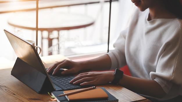 Cropped wizerunek pisać na maszynie na komputerowej pastylce z klawiaturową skrzynką piękna kobieta podczas gdy siedzący przy uporządkowanym drewnianym stołem nad żywym pokojem