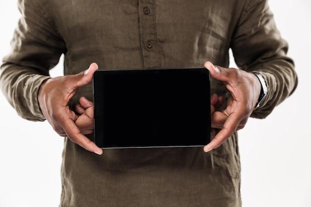 Cropped wizerunek pokazuje pustego pastylka ekran komputerowego afrykański mężczyzna