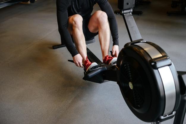Cropped wizerunek sportowy mężczyzna używa wioślarską maszynę