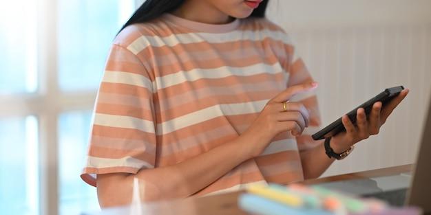 Cropped wizerunek trzyma smartphone w ona ręki student uniwersytetu. kobieta relaksuje z telefonu komórkowego pojęciem w domu.