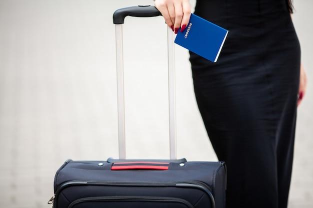 Cropped wizerunku podróżnika turystyczna kobieta krzyżował nogi w lecie z walizką na drodze w mieście plenerowym.