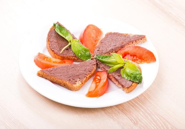 Crostini z oliwkową tapenadą, bazylią i pomidorem na talerzu