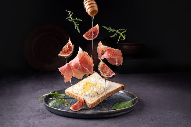 Crostini z prosciutto ricotta i figami, latająca włoska szynka i owoce na ciemnym tle, tosty z jamonem, zbliżenie.