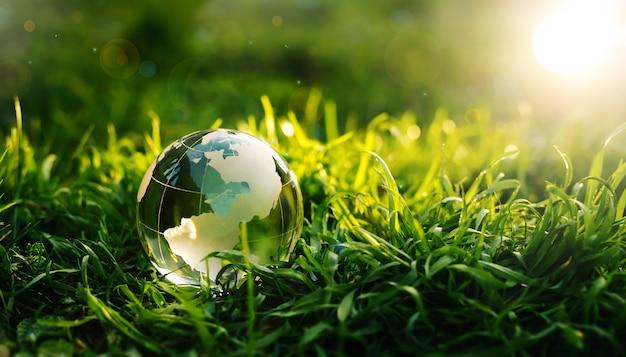 Crystal planet earth na zielonej trawie o zachodzie słońca koncepcja ochrony środowiska i dzień ziemi
