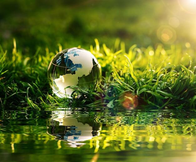Crystal planet earth w refleksji na zielonej trawie o zachodzie słońca koncepcja ochrony środowiska i dnia ziemi