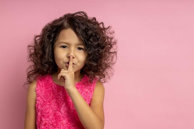 Ćś. zachowaj nasz mały sekret. portret dziewczyny w pięknej sukience, z kręconymi fryzurami, brązową skórą, wykonująca cichy gest, trzymając palec wskazujący na ustach, stoi. skopiuj miejsce.