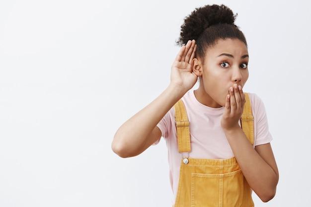 Ćśś, nie słyszę szeptów. zaintrygowana i zdumiona stylowa afroamerykanka w żółtym kombinezonie, z dłonią blisko ucha, podsłuchująca lub podsłuchująca szokującą rozmowę