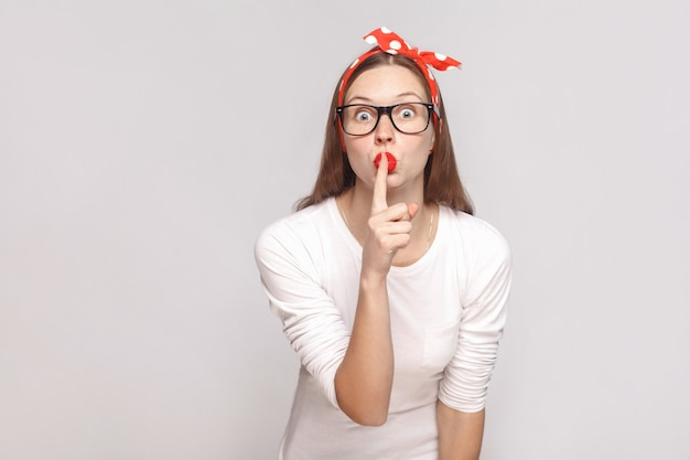 Ćśś! to jest tajemnica. portret pięknej emocjonalnej młodej kobiety w białej koszulce z piegami, czarne okulary, czerwone usta i opaska na głowę. kryty strzał studio, na białym tle na jasnoszarym tle.