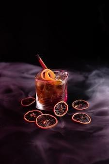 Cuba libre koktajl z rumem i colą w krótkim kieliszku z cynamonem i pomarańczowym czarnym tłem