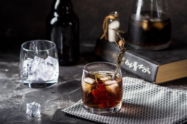Cuba libre lub mrożona koktajl z długiej wyspy z mocnymi napojami, colą, limonką i lodem w szklance, zimnym napojem lub lemoniadą. koktajl z ogniem. koktajl z dymem.