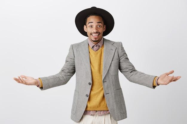 Cud może się zdarzyć. portret zadowolonego, sympatycznego studenta afroamerykańskiego w stylowym stroju, rozkładającego ręce i szeroko uśmiechającego się, szczęśliwego, pokazującego wiele możliwości