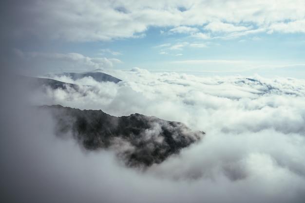 Cudowna alpejska sceneria ze wspaniałymi skałami i górami w gęstych niskich chmurach. klimatyczny krajobraz wyżyn z górskimi szczytami nad chmurami. piękny widok na ośnieżone szczyty górskie nad gęstymi chmurami.